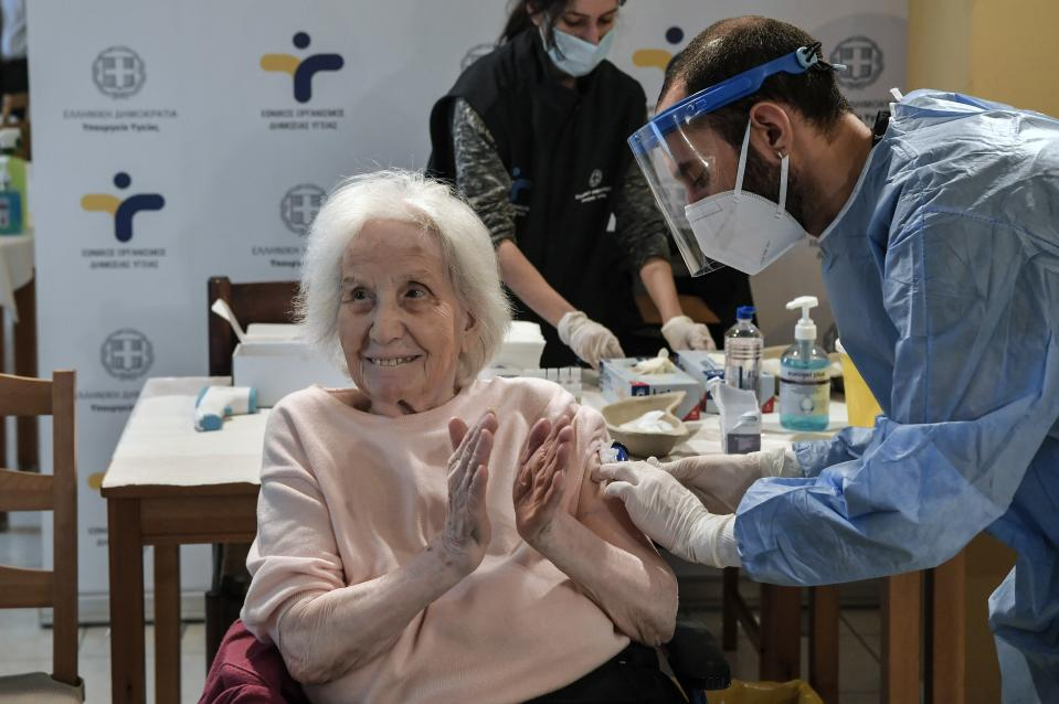 An elderly woman applauds during a vaccination at a nursing house in Athens, Monday, Jan. 4, 2021. Vaccinations were expanded from 9 to 50 hospitals nationwide on Monday. (Louisa Gouliamaki/Pool via AP)
