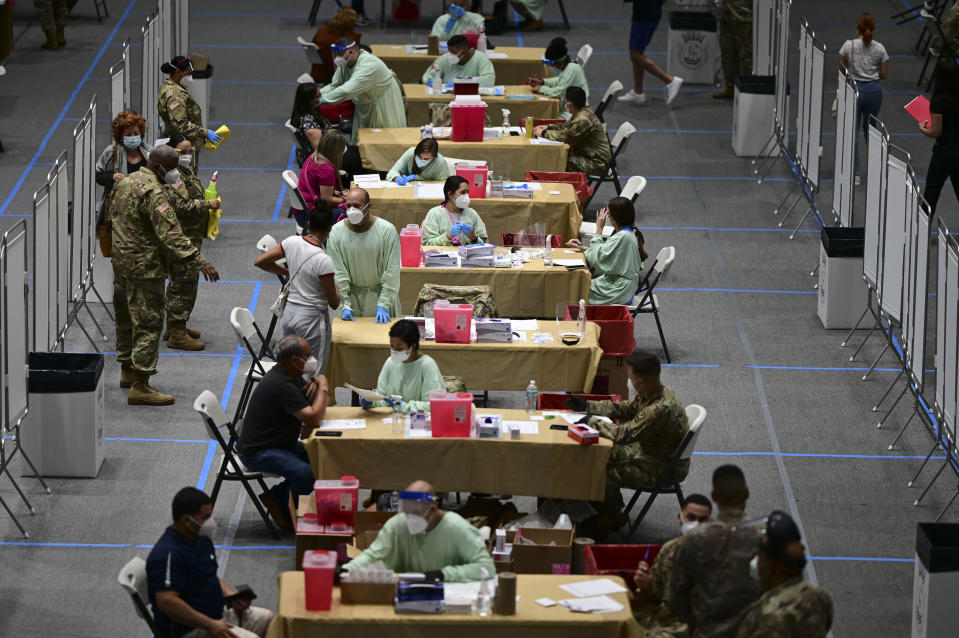 Health workers get vaccinated for COVID-19 at the Pedrin Zorrilla Coliseum in San Juan, Puerto Rico, Wednesday, Dec. 30, 2020. (AP Photo/Carlos Giusti)