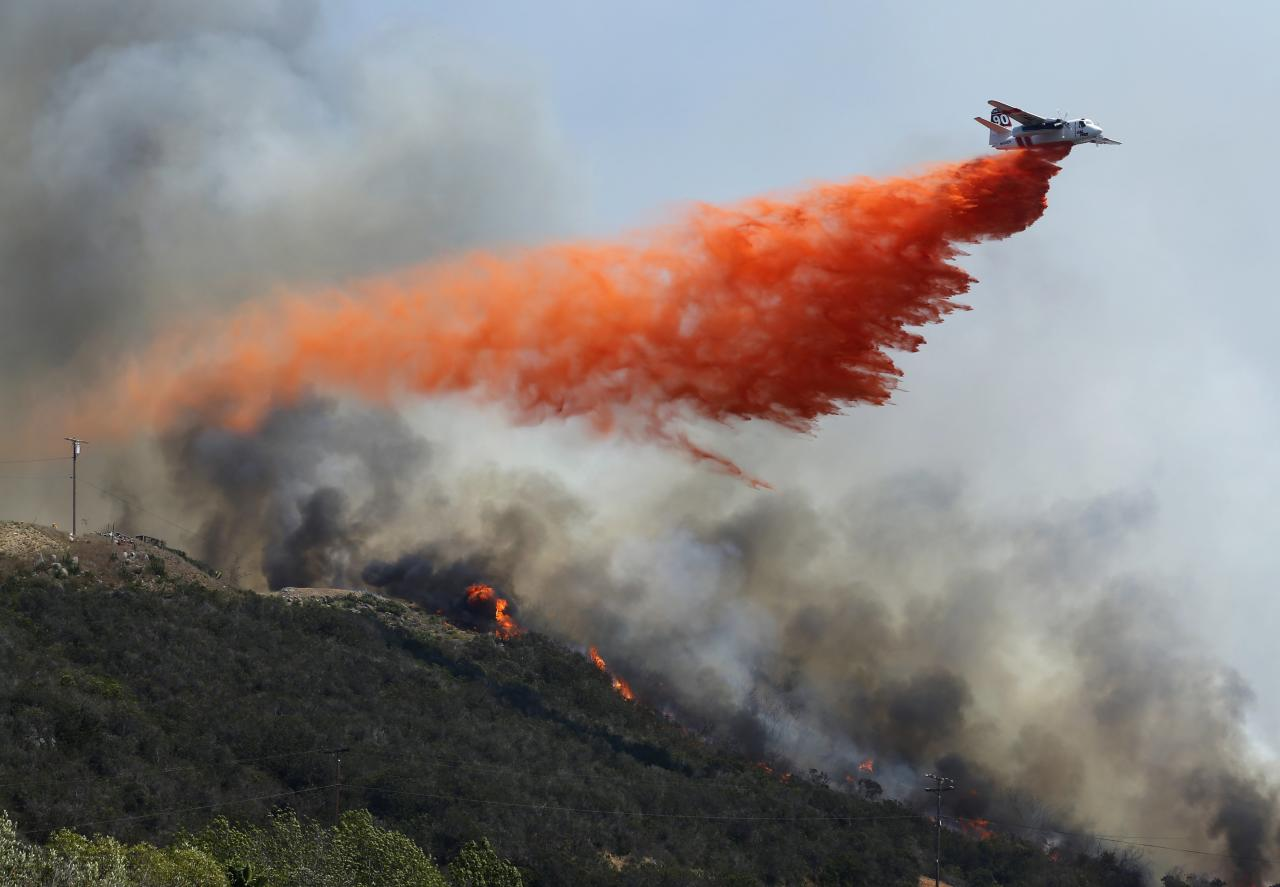 A water bomber makes a drop on flames burning on a hillside as the Cocos Fire continues in San Marcos, California May 15, 2014. Wildfires were raging in southern California on Thursday, keeping thousands of residents and students away from their homes after San Diego county officials maintained evacuation advisories. REUTERS/Mike Blake (UNITED STATES - Tags: ENVIRONMENT DISASTER)