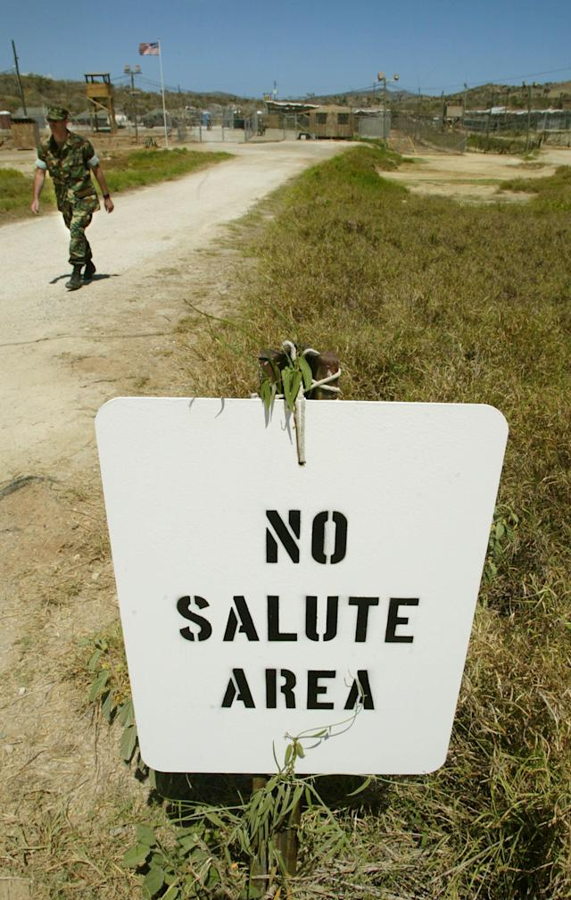 """404437 04: A soldier walks past a """"No Salute Area"""" sign, posted to keep the ranks of military officers secret from detainees, at Camp X-Ray April 24, 2002 in Guantanamo Bay, Cuba. Some 300 alleged Taliban and al Qaeda detainees have been brought to Camp X-Ray from Kandahar, Afghanistan. The detainees will soon be moved to Camp Delta which is expected to be finished within days. (Photo by Mario Tama/Getty Images)"""