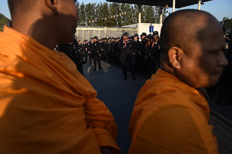 Buddhist monks face the police in front of the scandal-hit Wat Dhammakaya temple (AFP Photo/LILLIAN SUWANRUMPHA)