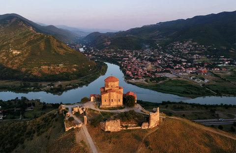 The Jvari monastery glowing in the first light of day. Beneath the monastery lies the confluence of the Mtkvari and Aragvi rivers. In the background is Mtskheta, the ancient capital of Georgia. - Credit: Amos Chapple/RFE/RL
