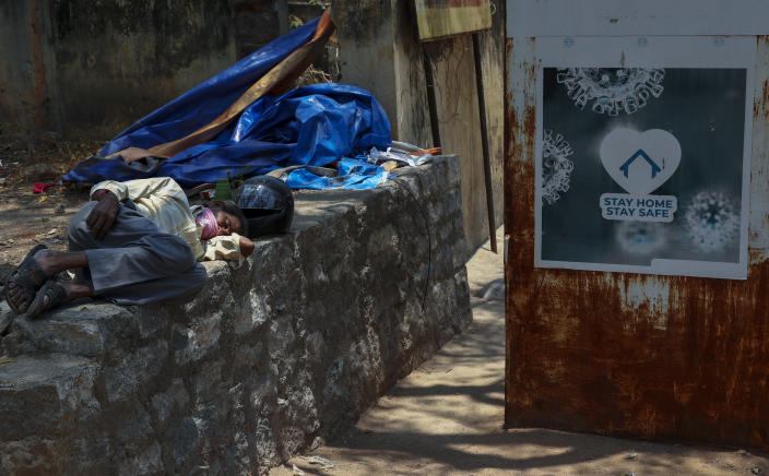 An Indian man sleeps next to a signage urging people to stay at home as a precaution against coronavirus in the premises of a hospital in Hyderabad, India, Thursday, April 29, 2021.(AP Photo/Mahesh Kumar A.)