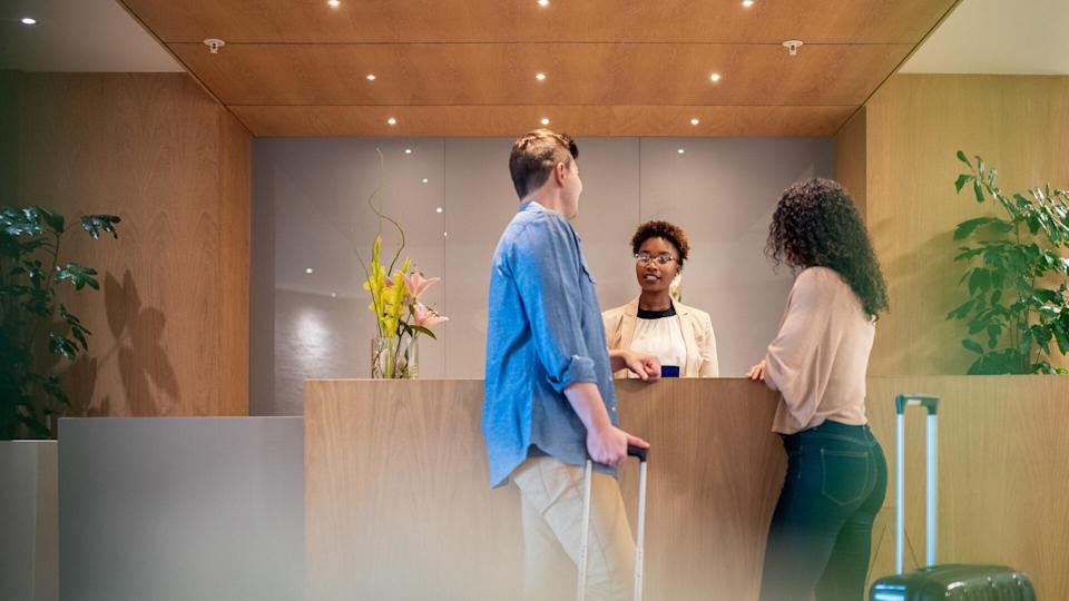 Mid adult couple talking to female receptionist.