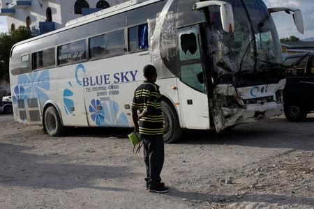 A man looks at a bus, which drove into a parade of pedestrians, parked in the police station of Gonaives,