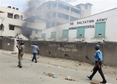 Armed policemen walk past Salvation Army Church compound set on fire by youths after protest against killing of Islamic cleric in Mombasa