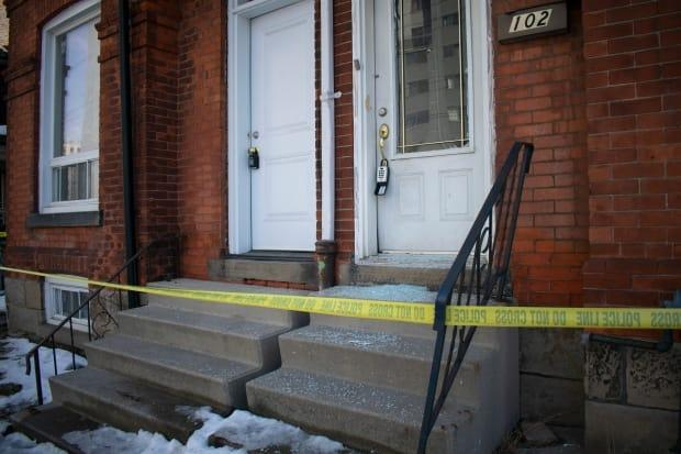 Police tape stretches across the front of 104 and 102 Wellington Street North. The front door at 104 was ajar and shattered glass littered the stairs of 102.