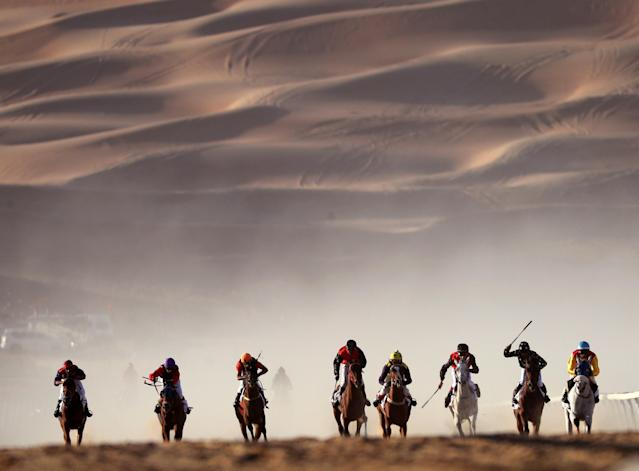 <p>Jockeys compete in a race for purebred Arab horses during the Moreeb Dune Festival on Jan. 1 in the Liwa desert, some 250 kilometers west of Abu Dhabi. (Photo: Karim Sahib/AFP/Getty Images) </p>