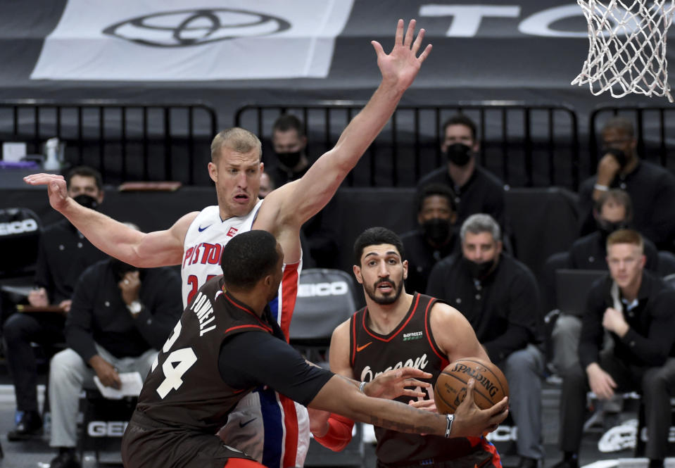 Portland Trail Blazers forward Norman Powell, front left, passes the ball around Detroit Pistons center Mason Plumlee, center, to center Enes Kanter during the second half of an NBA basketball game in Portland, Ore., Saturday, April 10, 2021. The Blazers won 118-103. (AP Photo/Steve Dykes)