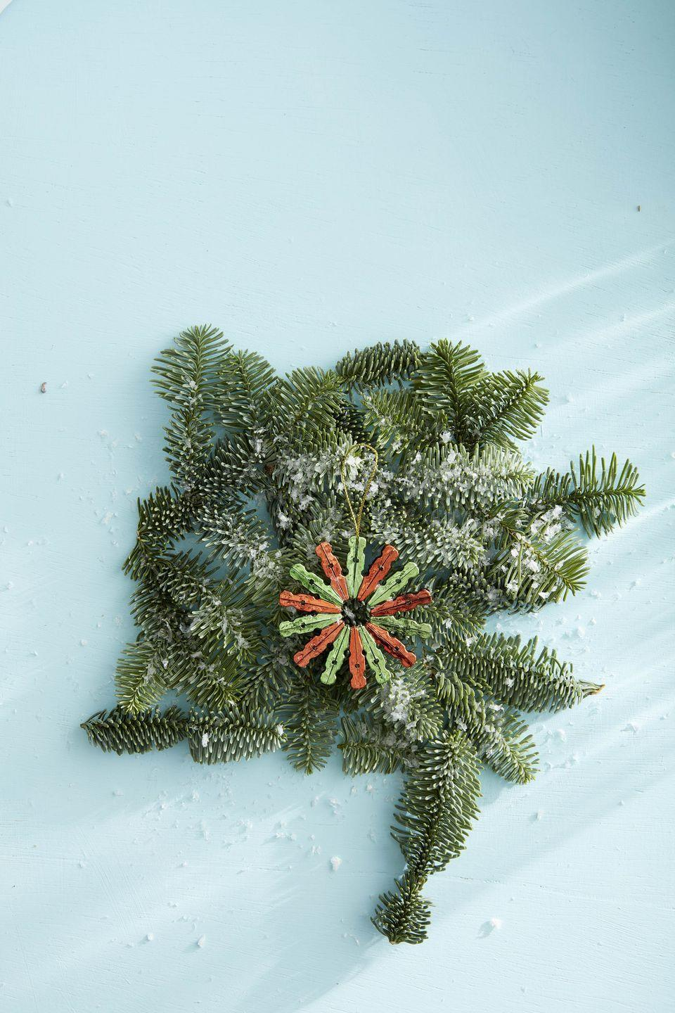 """<p>Turn a classic country item, the clothespin, into a sweet Christmas ornament. Our version is made with mini clothespins, but you can use the regular sized variety if you prefer.</p><p><strong>To make:</strong> Remove the springs from 14 mini clothespins. Turn the pieces from each clothespin around and glue them back to back. Glue the pins together to create a circular shape. Glue a piece of gold twine to one pin for hanging.</p><p><a class=""""link rapid-noclick-resp"""" href=""""https://www.amazon.com/JABINCO-Wooden-Colored-clothespins-coloers/dp/B0829HX6MQ/ref=sr_1_6?tag=syn-yahoo-20&ascsubtag=%5Bartid%7C10050.g.1070%5Bsrc%7Cyahoo-us"""" rel=""""nofollow noopener"""" target=""""_blank"""" data-ylk=""""slk:SHOP MINI CLOTHESPINS"""">SHOP MINI CLOTHESPINS</a></p>"""