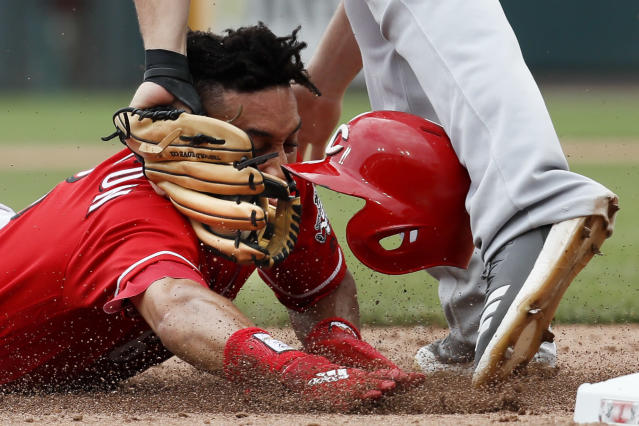 Cincinnati Reds' Billy Hamilton is tagged out at third by Milwaukee Brewers third baseman Mike Moustakas in the eighth inning of a baseball game, Thursday, Aug. 30, 2018, in Cincinnati. (AP Photo/John Minchillo)
