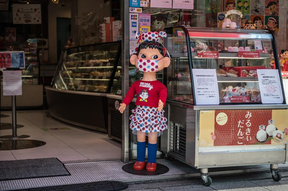 TOKYO, JAPAN - APRIL 28: An advertising doll wears a face mask as it is displayed in a shopfront in Ginza shopping district during a nationwide a state of emergency in which many shops, restaurants, cafes and businesses have closed, on April 28, 2020 in Tokyo, Japan. Japan has begun to see a slow down in Covid-19 coronavirus infections after several weeks under a state of emergency intended, amongst other things, to reduce person-to-person contact. The country has so far recorded 13,614 infections, 385 deaths and 1,899 recoveries from the virus. (Photo by Carl Court/Getty Images)