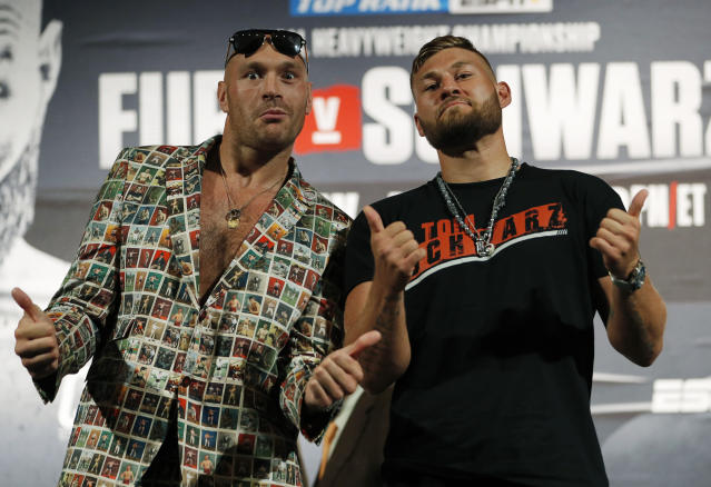 Tyson Fury, left, of England, and Tom Schwarz, of Germany, pose for photographers during a news conference for their upcoming fight Wednesday, June 12, 2019, in Las Vegas. The two are scheduled to fight in a heavyweight bout Saturday in Las Vegas. (AP Photo/John Locher)