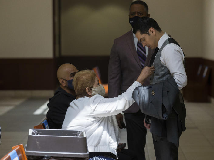 Victor Hugo Cuevas, a 26-year-old linked to a missing tiger named India, gets his tie adjusted by his grandmother, who did not wish to give her name, during a lunch break in the bond revocation hearing of a separate murder charge he's facing at Fort Bend County Justice Center on Friday, May 14, 2021, in Richmond, Texas. (Godofredo A. Vásquez/Houston Chronicle via AP)