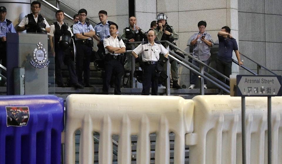 Police observe a protest outside their headquarters in Wan Chai from behind a set of large barricades in August of 2019. Photo: Edmond So