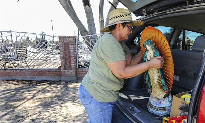 "Niland, Calif., resident Ana Valenzuela loads a Virgin Mary statue, one of her only possessions that survived the fire, into her car on Tuesday. <span class=""copyright"">(Eduardo Contreras / San Diego Union-Tribune)</span>"