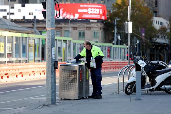 A man from a city cleaning crew tasked with sanitising public surfaces is seen in the Melbourne CBD.