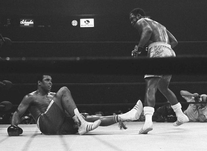 FILE - Joe Frazier stands over Muhammad Ali in the 15th round of their boxing match at Madison Square Garden in New York, in this March 8, 1971, file photo. They fought for 15 rounds, furiously at times, with Frazier moving forward in a crouch throwing big left hooks while Ali shot out fast jabs and right hands to counter him coming in.(AP Photo/File)