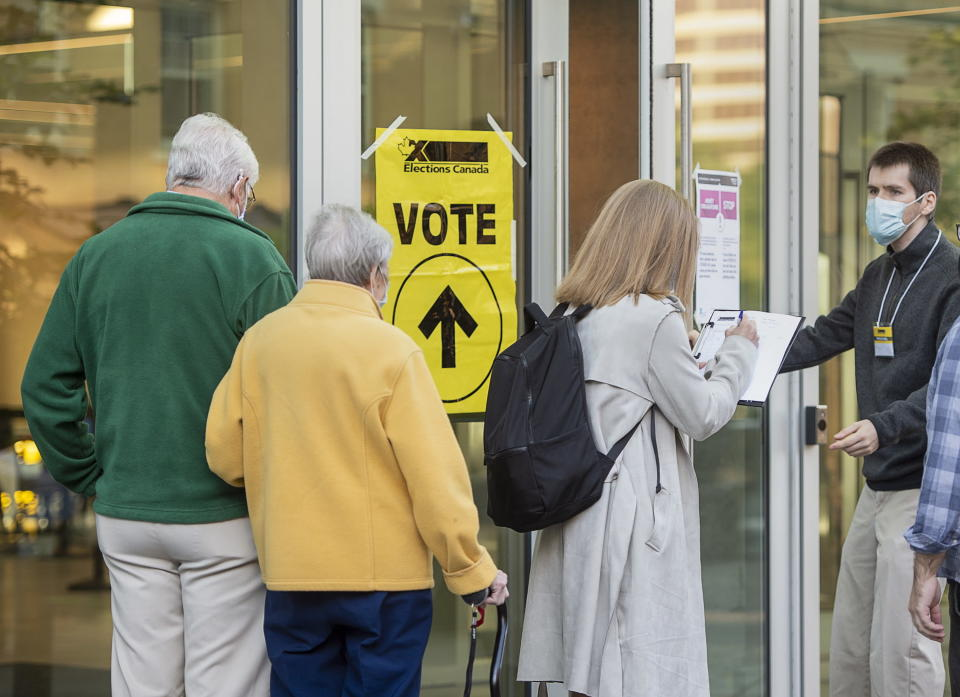 A voter provides COVID-19 contact-tracking information at the Halifax Convention Centre as they prepare to vote in the federal election in Halifax on Monday, Sept. 20, 2021. (Andrew Vaughan/The Canadian Press via AP)