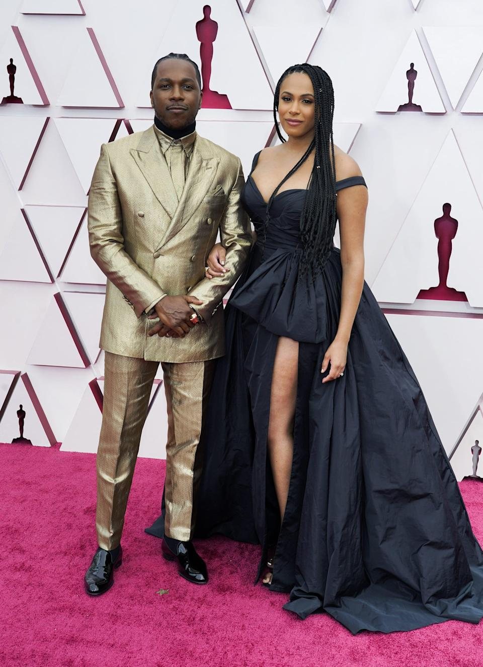 <p>Leslie Odom Jr. is wearing a shiny gold Brioni suit with a Cartier and Omega timepiece. Nicolette Robinson is wearing Zuhair Murad.</p>