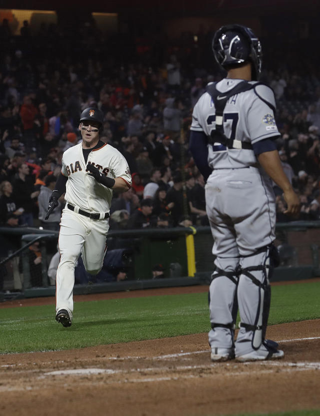 San Francisco Giants' Tyler Austin, left, runs toward home to score against the San Diego Padres during the fourth inning of a baseball game in San Francisco, Monday, April 8, 2019. Padres catcher Francisco Mejia, right, looks on. (AP Photo/Jeff Chiu)