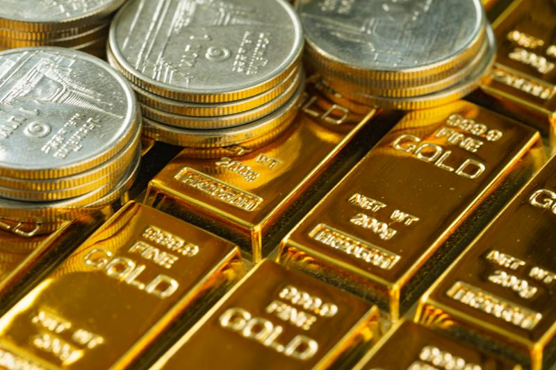 selective focus on shiny gold bars with stack of coins as business or financial investment and wealth concept.