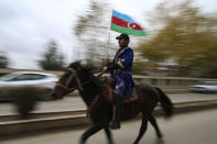 An Azerbaijani man holds a national flag riding a horse as he celebrates the transfer of the Lachin region to Azerbaijan's control, as part of a peace deal that required Armenian forces to cede the Azerbaijani territories they held outside Nagorno-Karabakh, in Aghjabadi, Azerbaijan, Tuesday, Dec. 1, 2020. Azerbaijan has completed the return of territory ceded by Armenia under a Russia-brokered peace deal that ended six weeks of fierce fighting over Nagorno-Karabakh. Azerbaijani President Ilham Aliyev hailed the restoration of control over the Lachin region and other territories as a historic achievement. (AP Photo/Emrah Gurel)