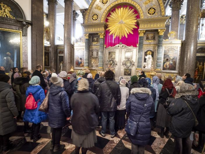 Orthodox believers gather for Sunday's prayer in the Kazansky Cathedral in St.Petersburg, Russia, Sunday, March 29, 2020. The leader of the Russian Orthodox Church is calling on believers to stay away from churches during the coronavirus pandemic and to pray at home instead. The new coronavirus causes mild or moderate symptoms for most people, but for some, especially older adults and people with existing health problems, it can cause more severe illness or death. (AP Photo/Dmitri Lovetsky)