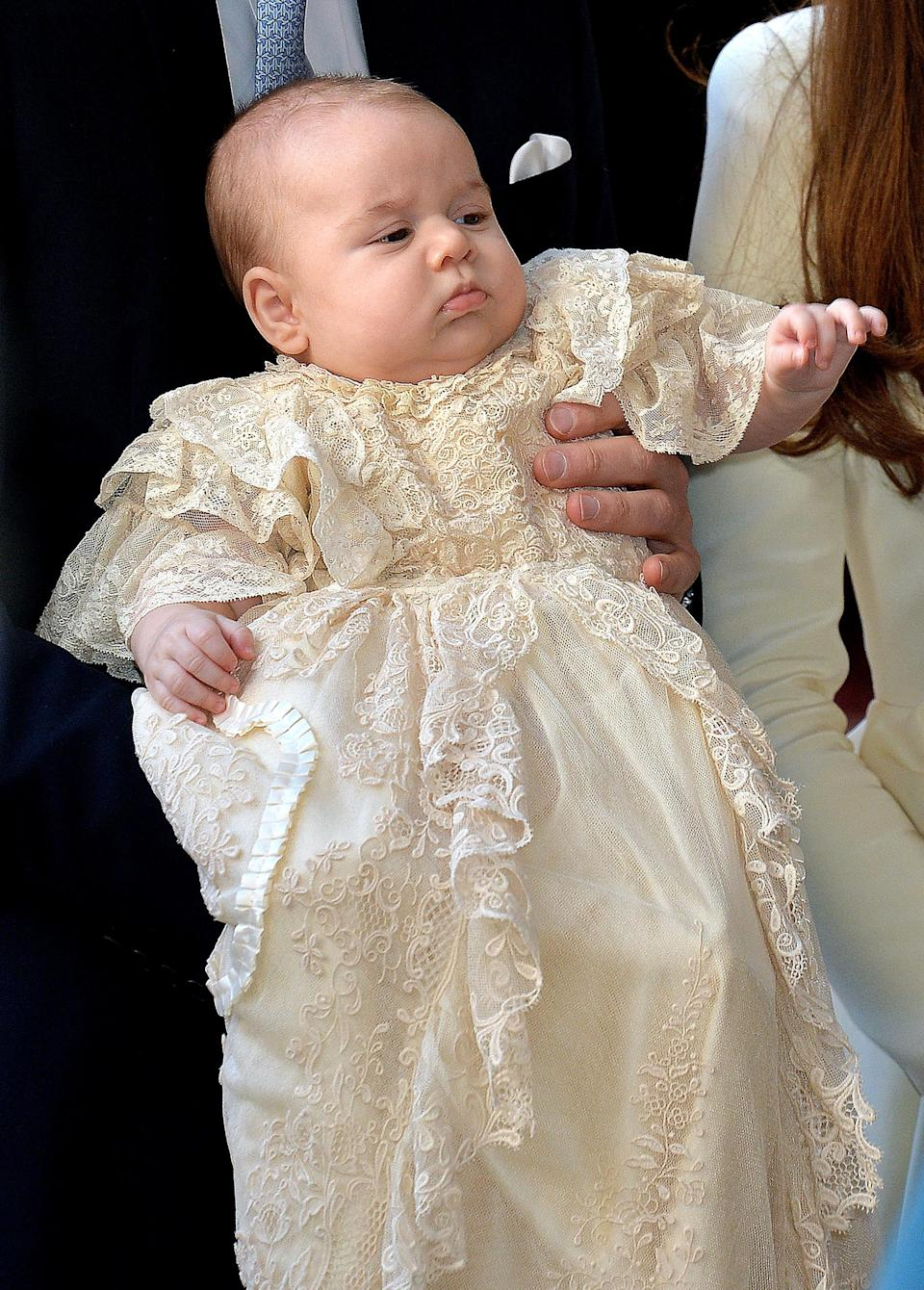 Prince George wearing the Honiton lace and white satin gown at his christening in October 2013. [Photo: Getty]