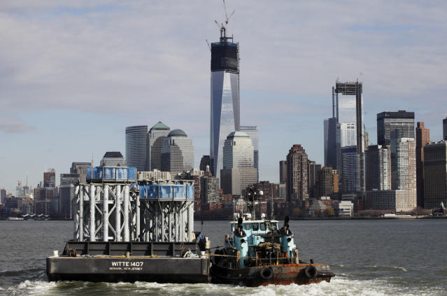 A barge loaded with sections of spire for One World Trade Center, left, is guided by tugboat across New York Harbor from New Jersey's Port Newark, Tuesday, Dec. 11, 2012 in New York. The nine pieces each weigh 70 tons. The spire is expected to rise into the Manhattan sky by spring. (AP Photo/Mark Lennihan)