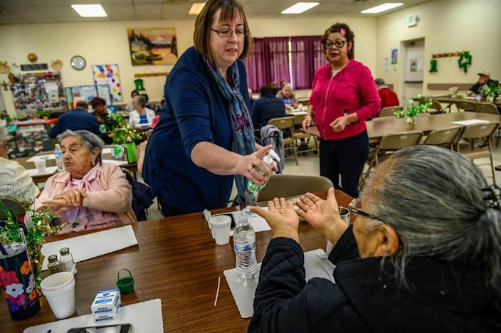 Julie Rhoten, executive director of the Stanford Settlement Neighborhood Center, passes out hand sanitizer to seniors after talking to them about safety precautions for the coronavirus on Monday, March 9, 2020, in Sacramento.