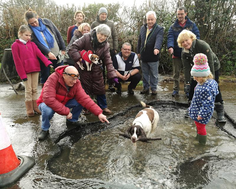 The town councillors and friends in and around the giant pothole in Buckfastleigh, Devon; See SWNS story SWPLpotholes; A group of councillors have dressed up with fishing rods and swimming goggles around an enormous pothole to have a chuckle at the state of Devon's roads. Members of Buckfastleigh Town Council are photographed huddled around the massive hole on the outskirts of the Devon town. There are eight town councillors in the photo, one of whom is dangling the fishing rod inside the pothole while another has donned a pair of swimming goggles. A ninth is behind the camera taking the photo. The water-filled pothole is so big there is a dog with a stick and a young child standing inside.