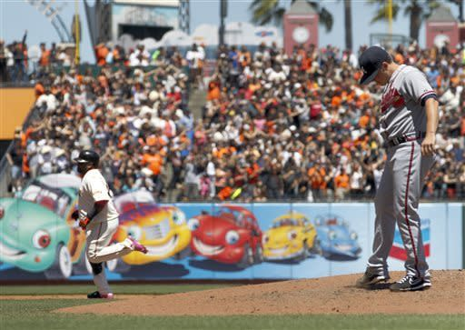 Atlanta Braves starting pitcher Kris Medlen, right, stands on the mound as San Francisco Giants' Pablo Sandoval, left, runs the bases after a solo home run during the third inning of a baseball game in San Francisco, Sunday, May 12, 2013. (AP Photo/Tony Avelar)