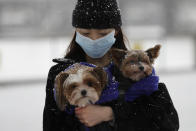 A woman holds her dogs during a snow flurry as temperatures dropped below freezing during the third coronavirus lockdown in London, Tuesday, Feb. 9, 2021. (AP Photo/Kirsty Wigglesworth)