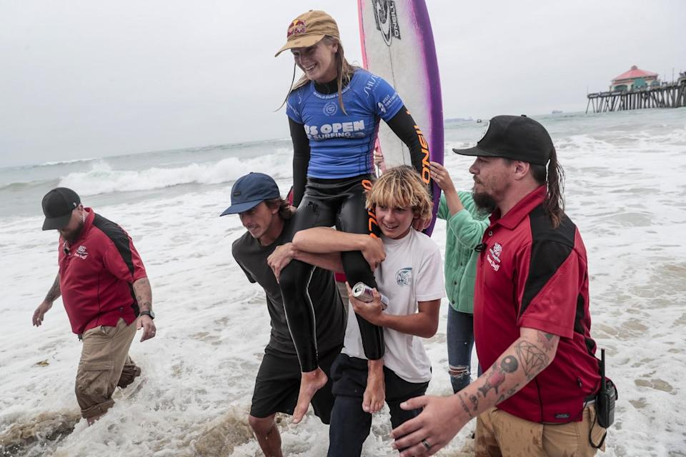 Caitlin Simmers is carried out of the surf after winning the final of the U.S. Open of Surfing at Huntington Beach.