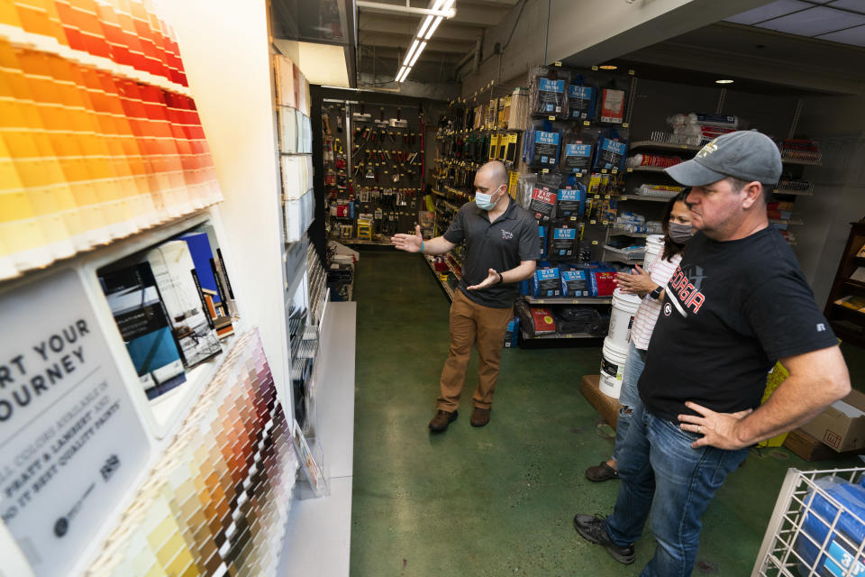 Billy Wommack, purchasing director at the W.S. Jenks & Sons hardware, left, works with customer Tim Wood, right, picking a paint color for an outdoor painting work at his house, Friday, Sept. 24, 2021, in northeast Washington. (AP Photo/Manuel Balce Ceneta)