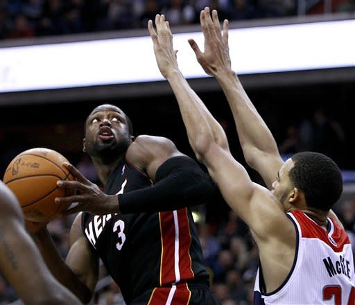 Miami Heat guard Dwyane Wade (3) eyes the basket as Washington Wizards center JaVale McGee (34) defends in the second quarter of an NBA basketball game in Washington, on Friday, Feb. 10, 2012. The Heat won 106-89. (AP Photo/Jacquelyn Martin)