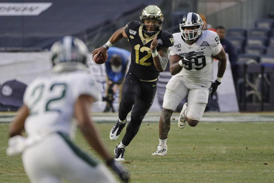 Michigan State's Raequan Williams (99) chases Wake Forest's Jamie Newman (12) during the first half of the Pinstripe Bowl NCAA college football game Friday, Dec. 27, 2019, in New York. (AP Photo/Frank Franklin II)