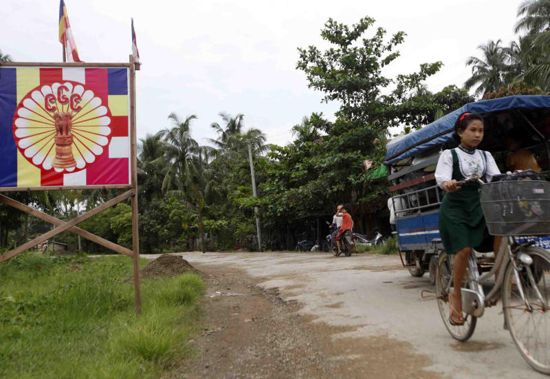 A school girl rides a bicycle past a 969 signboard, the logo of anti-Muslims movement in Myanmar, Wednesday, Oct. 2, 2013, in Thandwe, Rakhine State, western Myanmar. Terrified Muslim families hid in forests in western Myanmar on Wednesday, one day after rampaging Buddhist mobs killed a 94-year-old woman and burned dozens of homes despite the first trip to the volatile region by President Thein Sein since unrest erupted last year. The violence near Thandwe, a coastal town the president was due to visit later Wednesday on the second day of his tour of Rakhine state, raised new questions about government's failure to curb anti-Muslim attacks and or protect the embattled minority. (AP Photo/Khin Maung Win)