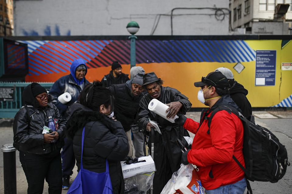 Felix Guzman, 52, of New York, wears protective gloves and a mask as he hands out gloves and sanitising wipes to people who are homeless. Source: AP