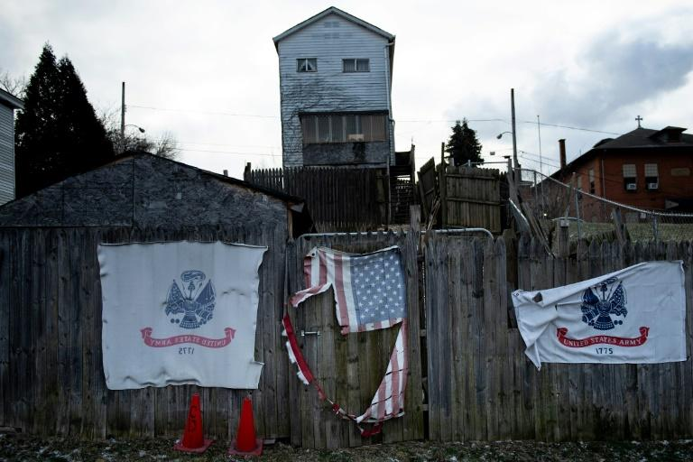 A home is seen with and American and US Army flags in North Braddock, Pennsylvania, part of the steel-making region that shifted sharply to Donald Trump in the 2016 presidential election (AFP Photo/Brendan Smialowski)