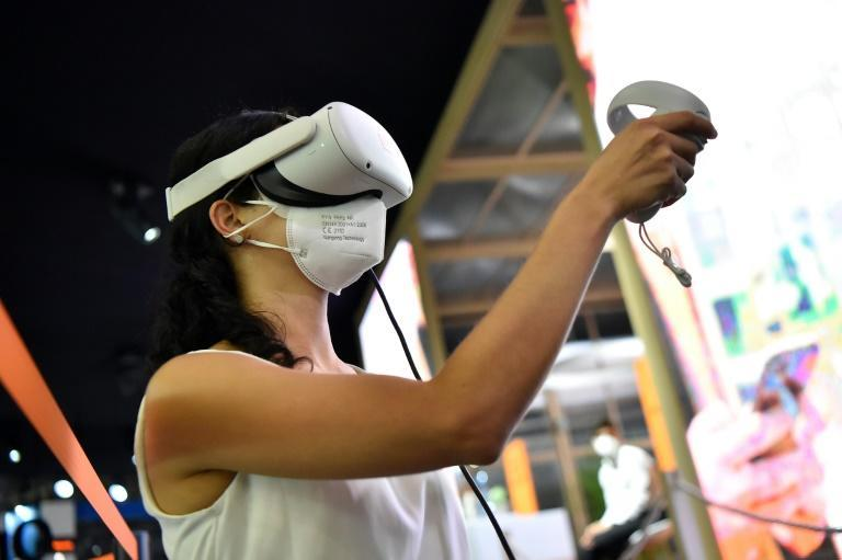 A woman tries virtual reality glasses at the Orange stand during the Mobile World Congress fair in Barcelona.