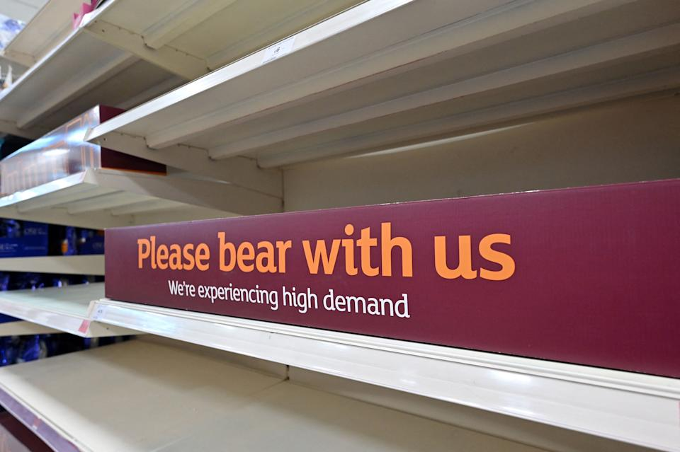 A sign requesting shoppers' patience about products temporarily out of stock is displayed on empty shelves in a supermarket at Nine Elms, south London on July 22, 2021. - British supermarkets and suppliers warned today of possible food shortages due to staff self-isolating, as rising coronavirus cases threaten chaos after the government controversially eased all restrictions earlier this week. (Photo by JUSTIN TALLIS / AFP) (Photo by JUSTIN TALLIS/AFP via Getty Images)