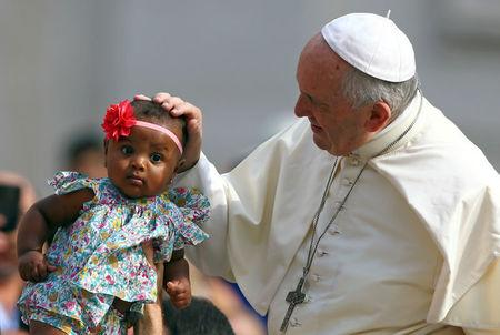FILE PHOTO: Pope Francis blesses a child as he arrives to lead the Wednesday general audience in Saint Peter's square at the Vatican