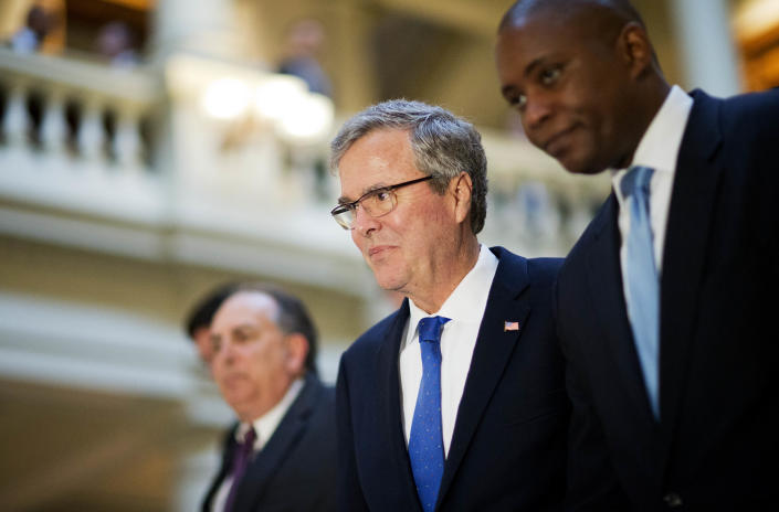 Former Florida Gov. Jeb Bush, left, walks with former campaign staff member Rufus Montgomery, right, while visiting the Georgia Capitol, Thursday, March 19, 2015, in Atlanta. (AP Photo/David Goldman)