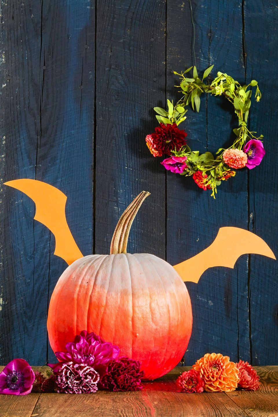 <p>Prop paper wings with chopsticks or skewers to help your pumpkin take flight (or at least look like it's about to). To get the multicolored paint job, strategically blend white, orange and magenta paint, adding more saturation from top to bottom. </p>