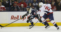 Columbus Blue Jackets' Alexander Wennberg, left, of Sweden, carries the puck up ice as Washington Capitals' Christian Djoos, of Sweden, defends during the second period of an NHL hockey game Tuesday, Feb. 12, 2019, in Columbus, Ohio. (AP Photo/Jay LaPrete)