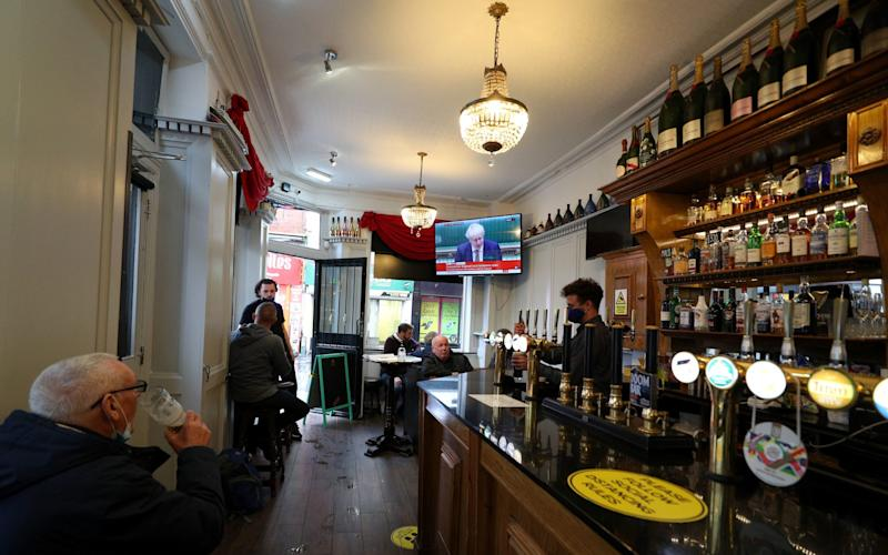 People in the Richmond pub in Liverpool watch a statement by the Prime Minister Boris Johnson - Peter Byrne/PA Wire