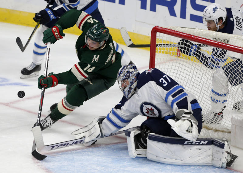Winnipeg Jets goalie Connor Helebuyck (37) makes a save on a shot by Minnesota Wild center Joel Eriksson Ek in the second period of a hockey game Sunday, Sept. 29, 2019 in St. Paul, Minn. (AP Photo/Andy Clayton-King)