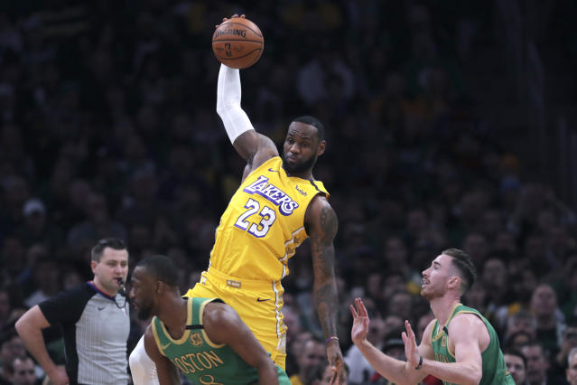 Los Angeles Lakers forward LeBron James (23) leaps for a pass as he is covered by Boston Celtics forward Gordon Hayward (20) during the first half of an NBA basketball game in Boston, Monday, Jan. 20, 2020. (AP Photo/Charles Krupa)